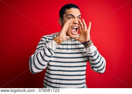 Young brazilian man wearing casual striped t-shirt standing over isolated red background Shouting angry out loud with hands over mouth