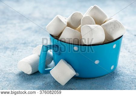 Mug Filled With Marshmallows On Blue Background Copy Space