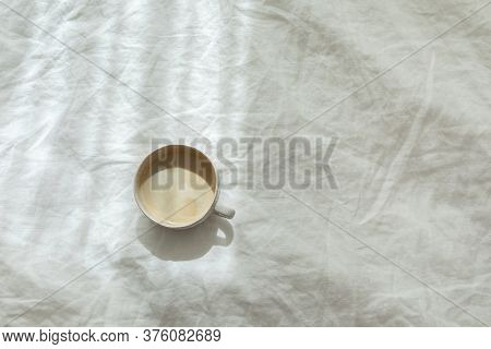 Cup Of Fresh Coffee On Texture Of Linen Cotton Rough Textile Bedclothes. Morning Mood. Cappuccino In