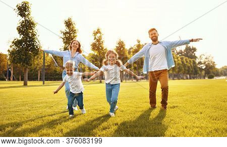 Excited Parents And Children Smiling With Outstretched Arms Towards Camera On Green Lawn In Summer P