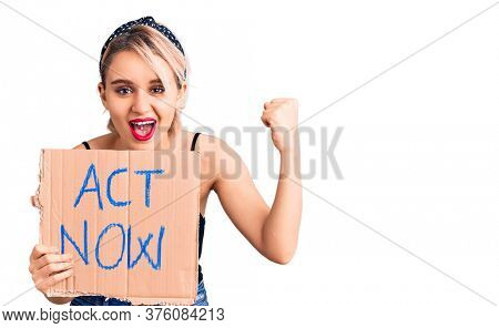 Young beautiful blonde woman holding act now banner screaming proud, celebrating victory and success very excited with raised arms