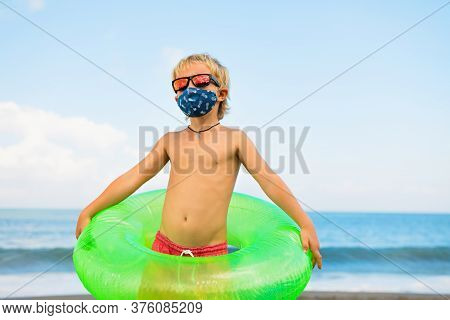Funny Child In Sunglasses, Inflatable Ring On Tropical Sea Beach. New Rules To Wear Cloth Face Cover
