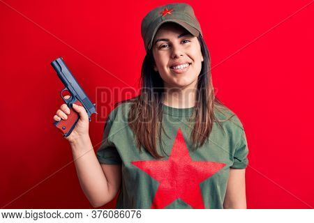 Young beautiful brunette woman wearing t-shirt with red star communist symbol holding gun looking positive and happy standing and smiling with a confident smile showing teeth