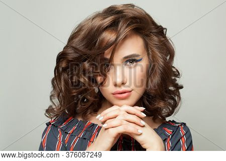 Attractive Woman With Clear Skin And Dark Curly Bob Hairdo On White