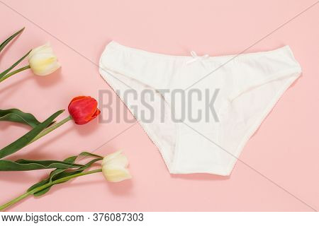White Cotton Panties With Tulip Flowers On A Pink Background. Woman Underwear Set. Top View.