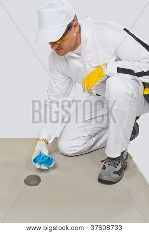 Worker With Glass Flask Of Water Testing The Humidity Of Cement Base