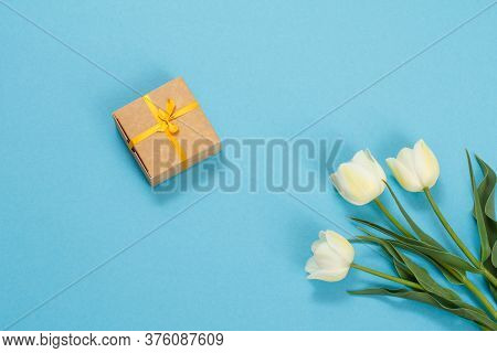 Brown Gift Box With Beautiful Yellow Tulips On A Blue Background. Top View. Concept Of Giving A Gift