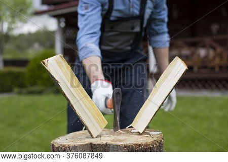 Close Up Strong Man Lumberjack In Uniform Chopping Wood With Sharp Ax On Wooden Hemp, Sawdust Fly To