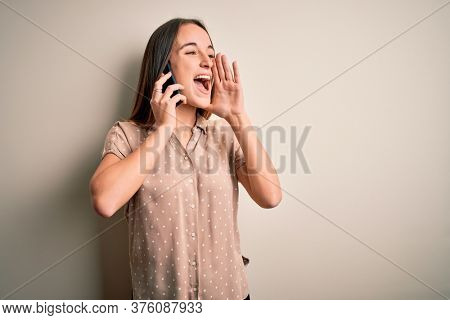 Young beautiful woman having conversation talking on the smartphone over white background shouting and screaming loud to side with hand on mouth. Communication concept.