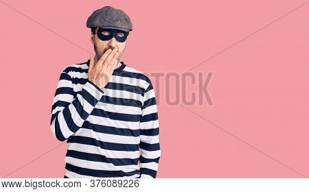Middle age handsome man wearing burglar mask bored yawning tired covering mouth with hand. restless and sleepiness.