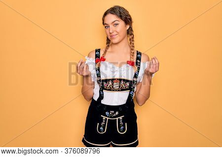 Young beautiful blonde german woman with blue eyes wearing traditional octoberfest dress doing money gesture with hands, asking for salary payment, millionaire business