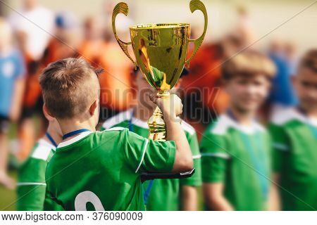 Group Of Young Boys Rising Up Golden Trophy For Winning Sports School Tournament. Happy Children Cel