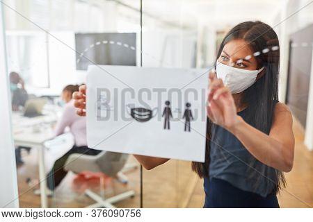 Business woman with everyday mask fastens notice board with rules of conduct against infection with Covid-19
