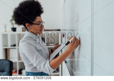Online English Course. Side View Of A Young Afro American Female Teacher Writing On A Whiteboard Whi