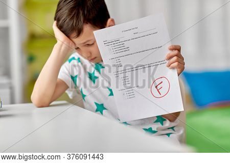 children, education and learning concept - sad student boy with failed school test at home