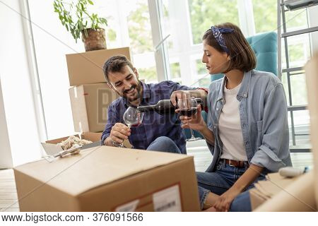 Beautiful Young Couple In Love Moving In New Apartment, Celebrating By Opening A Bottle Of Wine And