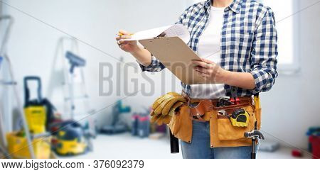 repair, construction and building concept - close up of woman or builder with clipboard, pencil and working tools on belt over utility room background