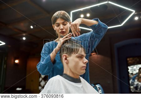 Young Professional Barber Girl Or Hairstylist With Scissors And Hair Comb In Hands Making Haircut Fo