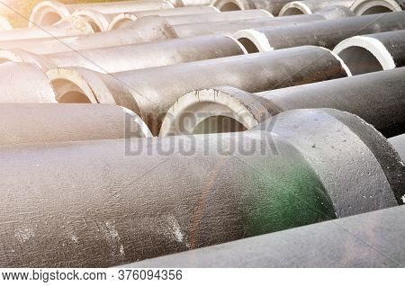Concrete Pipes Coated With Protective Mastic At A Construction Site.