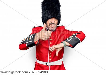 Middle age handsome wales guard man wearing traditional uniform over white background Doing thumbs up and down, disagreement and agreement expression. Crazy conflict
