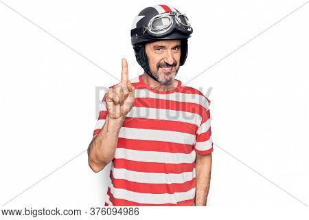 Middle age handsome motorcyclist man wearing moto helmet over isolated white background smiling with an idea or question pointing finger up with happy face, number one