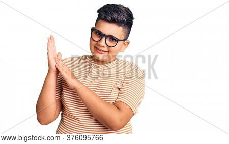 Little boy kid wearing casual clothes and glasses clapping and applauding happy and joyful, smiling proud hands together