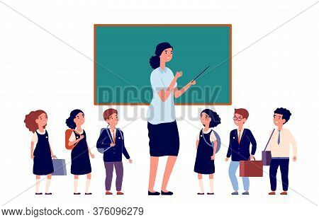 Teacher And Students. Elementary School Pupils. Young Lady Near Chalkboard And Preschool Or Primary