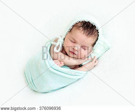 Cute newborn sleeping peacefully on tiny pillow