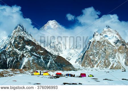 Tourist Camp In The Mountains Near Snow Peaks With Blue Sky And Beautiful Clouds