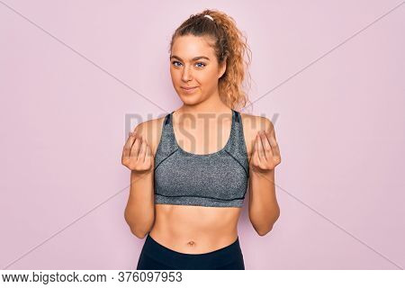 Young beautiful blonde sportswoman with blue eyes doing exercise wearing sportswear doing money gesture with hands, asking for salary payment, millionaire business