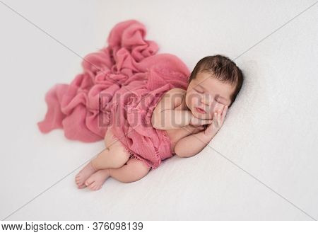 Beautiful sleeping newborn lying on side lightly covered with blanket