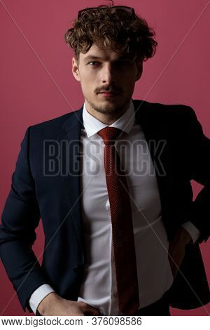 sexy young businessman tucking his shirt while posing on pink background