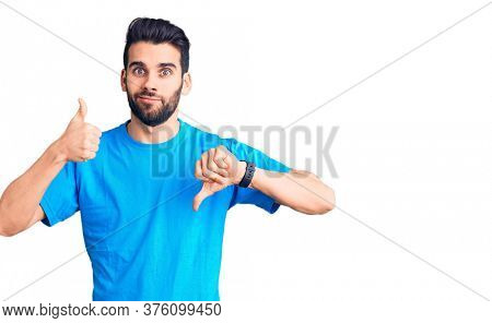 Young handsome man with beard wearing casual t-shirt doing thumbs up and down, disagreement and agreement expression. crazy conflict