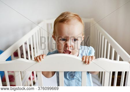 Baby Standing In Bed At Home. Portrait Of Baby Girl Stand In Cot. Baby Eyes Looking For Mother. Sad
