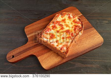 Delectable Homemade Tomato And Cheese Pizza Toast Isolated On Wooden Breadboard