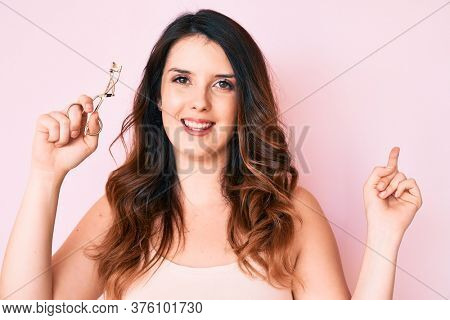 Young beautiful brunette woman holding eyelash curler smiling happy pointing with hand and finger to the side