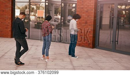 Full Body Modern People In Masks Using Smartphone And Keeping Social Distance While Standing In Queu