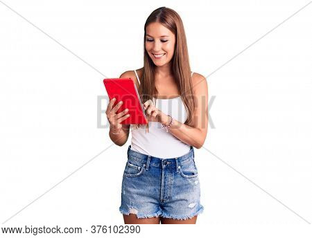 Young beautiful hispanic woman holding touchpad looking positive and happy standing and smiling with a confident smile showing teeth
