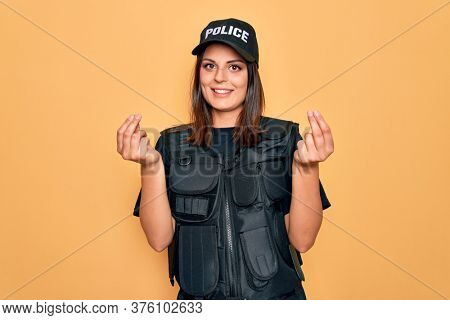 Young beautiful brunette policewoman wearing police uniform bulletproof and cap doing money gesture with hands, asking for salary payment, millionaire business