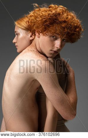 Touch. Fashion Portrait Of Beautiful Redhead Couple Isolated On Grey Studio Background. Concept Of M