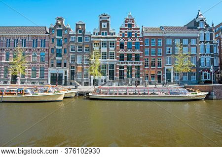 Medieval houses and cruise boats along the canal in Amsterdam the Netherlands