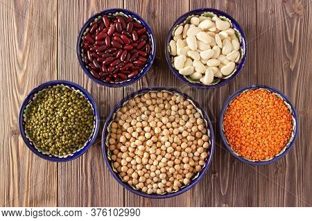 Different Legume: Raw Chickpea, Lentil, Mung, White And Red Bean In Bowls On Wooden Background. Top