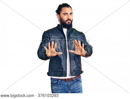 Young arab man wearing casual leather jacket moving away hands palms showing refusal and denial with afraid and disgusting expression. stop and forbidden.