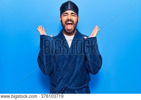 Young hispanic man wearing sleep mask and robe celebrating mad and crazy for success with arms raised and closed eyes screaming excited. winner concept