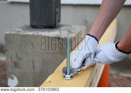 Gloved Hand Of Male Worker Tightens Screw Nut With Adjustable Metal Wrench In Wooden Board Construct