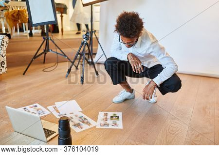 Photographer looks at photos for image selection on the floor in the photo studio