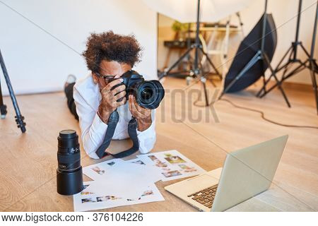 Young photographer with camera and print photos in the photo studio in front of the laptop