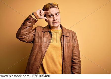 Young handsome redhead man wearing casual leather jacket over isolated yellow background worried and stressed about a problem with hand on forehead, nervous and anxious for crisis