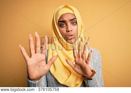Young beautiful african american girl wearing muslim hijab over isolated yellow background Moving away hands palms showing refusal and denial with afraid and disgusting expression. Stop and forbidden.
