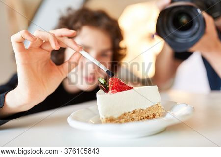 Stylist with brush and cake during food styling for a photo shoot